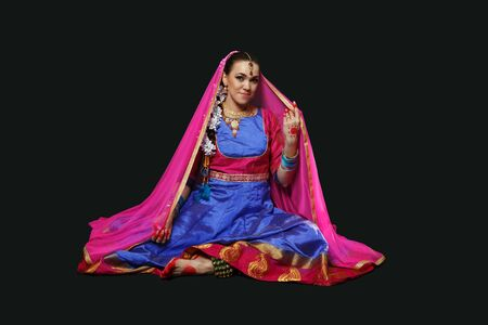A woman in an Indian suit. A beautiful girl in ornaments is dancing Indian dances.