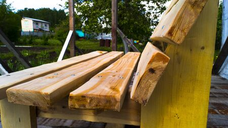 Side view of a handmade wooden bench. Garden furniture. Untreated wood. Rest in the country. Landscaping. Foto de archivo