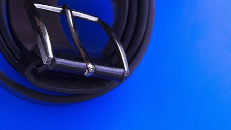 Black leather mens belt on a blue background. Metal plaque. The subject of style. Mens accessory. View from above. Place for text.