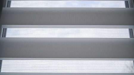 White roller blinds with stripes and mesh on a plastic window in the room. Day and night system.
