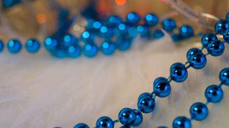 Blue Christmas beads on a light background, lit by lights of a garland. Template for a postcard. Christmas background. Place for text. Selective focus.