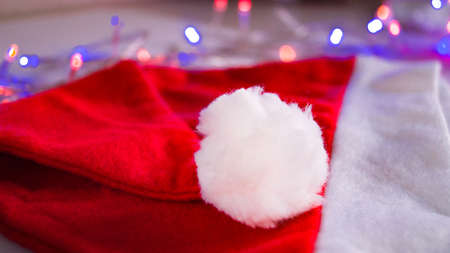 The red hat of Santa Claus with a white pampon lies on the background of a garland. Christmas and New Year. The attribute for overpayment. Place for text. Copy space. Selective focus.