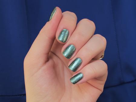 nailart: green glitter nails blue background Stock Photo