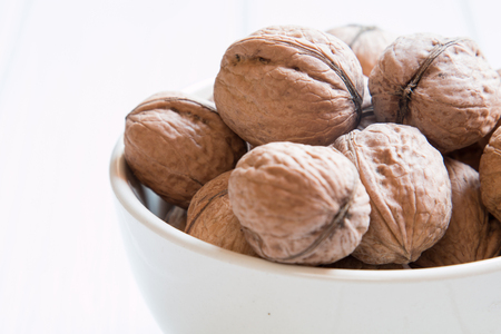 unsaturated: Whole walnuts close-up on a white table