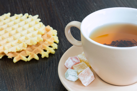 Light cup full of tea and saucer with sweets