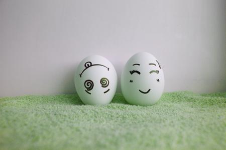 pareja comiendo: Los huevos son divertidos con las caras en la cabeza en verde Foto de archivo