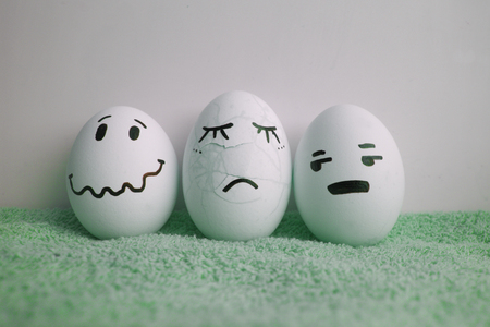 Eggs with faces. Crashed and cracked on a green
