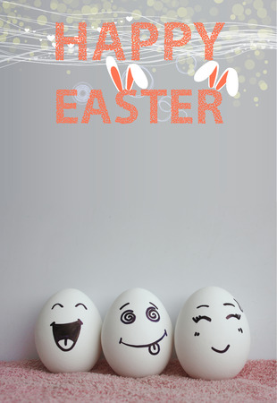 pareja comiendo: Eggs with faces painted on a gray background with an orange inscription Easter and rabbits behind it. Photo for your design with a place under the text Foto de archivo