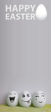 pareja comiendo: Huevos con rostros pintados sobre un fondo claro con una inscripción blanca de Pascua y un huevo blanco. Foto para su diseño con un lugar debajo del texto Foto de archivo
