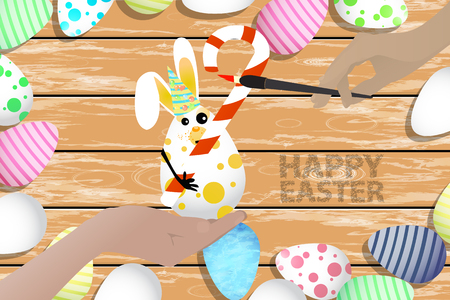 wooden stick: Easter is a perfect illustration for your design. Easter bunny - an egg with a candy in the form of a curled stick in the hands on the background of a wooden table in a pile of painted eggs
