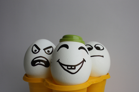 Eggs with a cute face. Photo for your design. three eggs. Concept: optimist, pissimist and realist