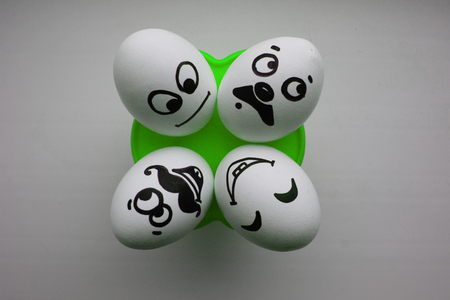 pareja comiendo: Eggs with a cute face. Photo for your design. Four eggs lie and look up. Concept: gossip