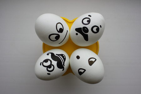 Eggs with a cute face. Photo for your design. Four eggs lie and look up. Concept: collusion