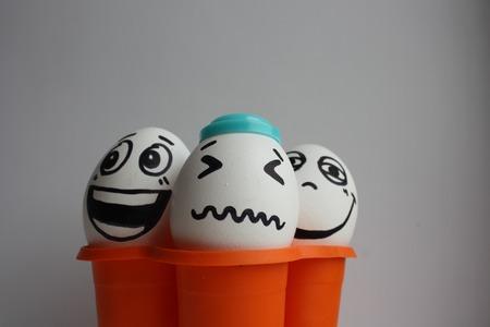 pareja comiendo: Eggs with a cute face. Photo for your design. three eggs. Concept: goose bumps in orange pack Foto de archivo