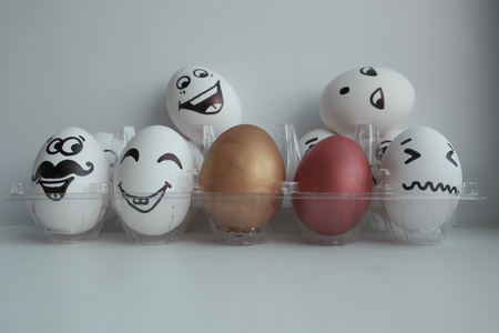 whites: Eggs Easter white group in a transparent box with cheerful and mischievous faces having fun and standing on the heads of neighbors and two colored eggs in the middle.