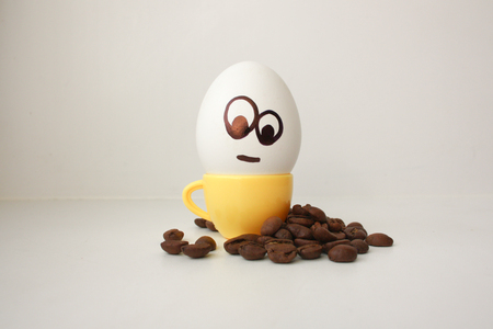 hot couple: Egg with a face. Funny and cute to a coffee mug with coffee beans around. Useful and invigorating breakfast. Photo for your design. Look down at the grains in meditation Stock Photo