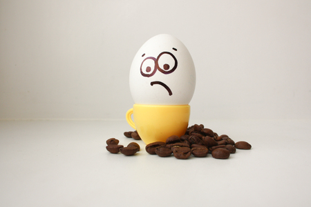 disposition: Egg with a face. Funny and cute to a coffee mug with coffee beans around. Useful and invigorating breakfast. Photo for your design. Angry and dissatisfied. Poor disposition of the spirit Stock Photo