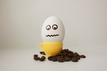 hot couple: Egg with a face. Funny and cute to a coffee mug with coffee beans around. Useful and invigorating breakfast. Photo for your design. I want to eat very much