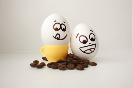 Egg with a face. Funny and cute to a coffee mug with coffee beans around. Useful and invigorating breakfast. Photo for your design. Joyful. Flirts showing the tongue. Cheerful company of two pieces