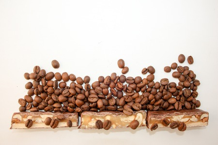 coveted: Sweet candy with a nut in coffee grains on a white background. A tasty and coveted photo for your design Stock Photo
