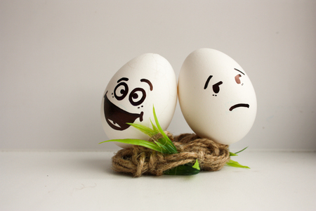 silly face: Eggs are funny muzzles. Two eggs fight for the nest. Joy and sadness. Photo for your design Stock Photo