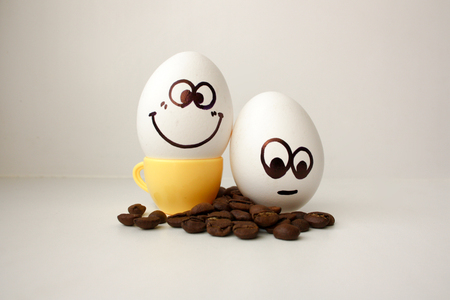An egg with a face. Funny and sweet. TWO EGGS. MORNING AND CUP OF COFFEE. NECESSARY. Photo for your design.
