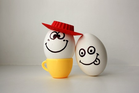 An egg with a face. Funny and sweet. SAD IN THE HAT. AMIGO. LOVE IS SAD AND FRIEND MERRY. SHOWS LANGUAGE, DRAZNIT. Photo for your design. Foto de archivo