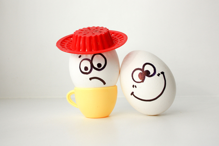 An egg with a face. Funny and sweet. SAD IN THE HAT. AMIGO. LOVE IS SAD AND FRIEND MERRY. FRIENDSHIP SURPRISES. Photo for your design.