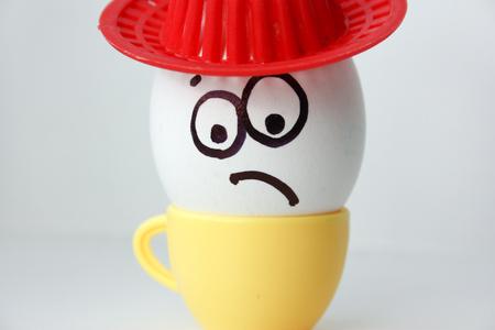 Un huevo con una cara. Divertido y dulce. TRISTE EN EL SOMBRERO. AMIGO. EL AMOR ES TRISTE para tu diseño. Foto de archivo