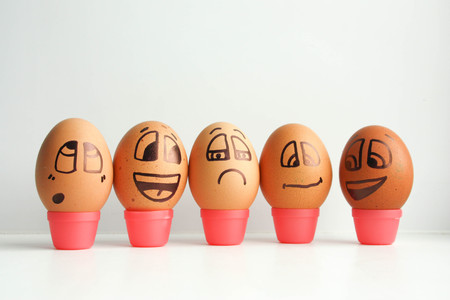 Cheerful eggs in a row, lined up in a semicircle. Photo for design. Eggs with painted face. Horizontal orientation of the sheet. Stock Photo