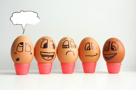 Cheerful eggs in a row, lined up in a semicircle. Thinking out loud. Place under the text. Photo for design. Eggs with painted face. Horizontal orientation of the sheet. Stock Photo