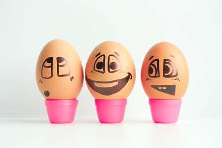 Cheerful eggs three friends, brown eggs. Photo for design. Eggs with painted face. Horizontal orientation of the sheet.