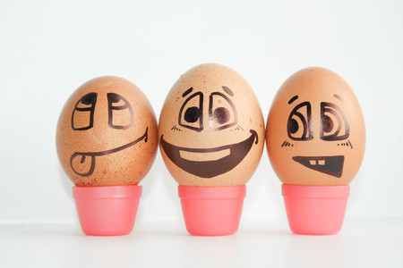 Cheerful eggs three friends, brown eggs. Shows the language and teases. Photo for design. Eggs with painted face. Horizontal orientation of the sheet. Stock Photo