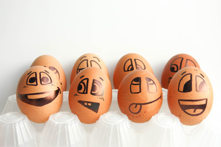 Cheerful eggs in two rows. The concept of the tribune of the fans. Photo for design. Eggs with painted face. Horizontal orientation of the sheet.