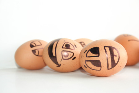 Merry eggs laugh, lie on the surface. Photo for design. Eggs with painted face. Horizontal orientation of the sheet.