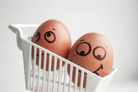 Shopping cart and two eggs playing hide and seek. An egg with a face. Photo for your design