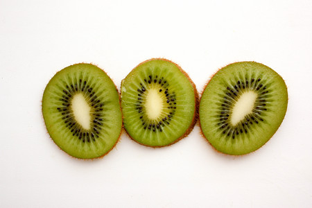 Kiwi green with black small bones. Three slices. Juicy in slicing. Unordinary inside. Photo for your design
