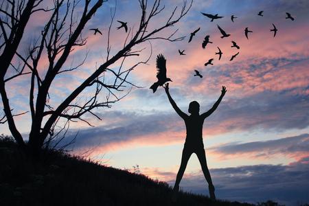 Concepto de libertad. La muchacha en un fondo de la puesta del sol deja los pájaros en el cielo. Ilustración para su diseño