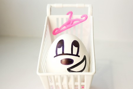 hangers: Shopping concept. A shopping basket for shopping and a clothes hanger. The egg is pleased with the painted face. on a white background. Photo for your design