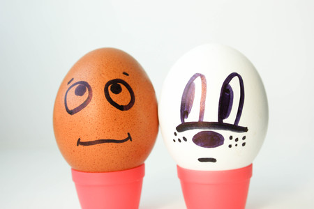 interracial: Interracial complexity of communication concept. Eggs with painted face. black and white. on a white background. Photo for your design