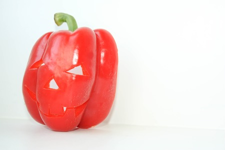 Halloween. Pumpkin with a terrible face. Red pepper on white background. Photo for your design