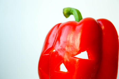 Halloween. Pepper red with an eerie face and slits between the eyes. on a white background. Photo for your design