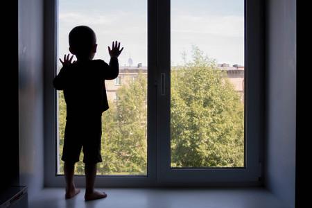 概念上の家庭内暴力。子供は、窓の外に見えます。オールインワン子の写真は窓の外に見えます。あなたのデザインの写真 写真素材