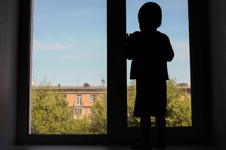 delinquent: Child deviant behavior concept. The child looks out the window. Photo for your design. The child looks out the window. Photo for your design Stock Photo