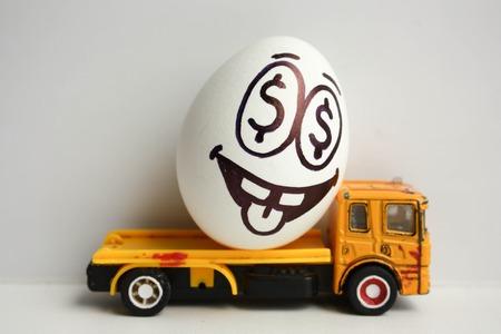 Bedrijfsconcept. Zakelijk vervoer. Gelukkig ei met een geschilderd gezicht op een gele auto. Foto voor uw ontwerp