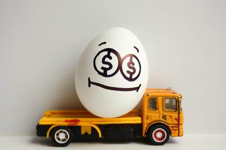 Bedrijfsconcept. Zakelijk vervoer. Een gelukkig ei met een geschilderd gezicht op een gele auto rijdt in de rug. Foto voor uw ontwerp