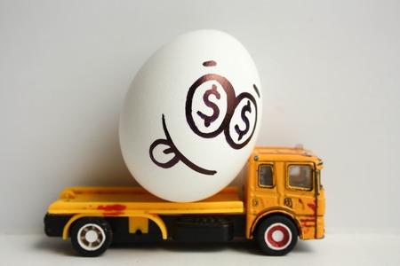 Bedrijfsconcept. Zakelijk vervoer. Een gelukkig ei met een geschilderd gezicht op een gele auto met zijn tong die uit hangt. Foto voor uw ontwerp Stockfoto
