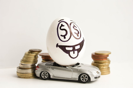 Business concept. Business car. An egg with a painted face and a tongue sticking out among the coins. Egg on a gray car. Photo for your design