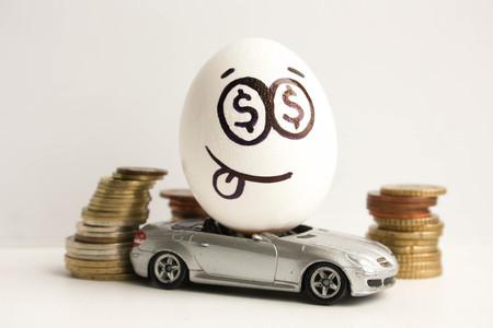 Bedrijfsconcept. Zakelijke auto. Een ei met een geschilderd gezicht en een kleverige tong in het midden van een stapel munten. Ei op een grijze auto. Foto voor uw ontwerp Stockfoto