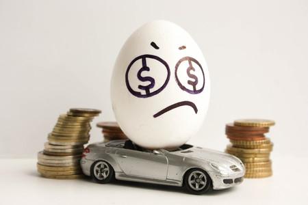Bedrijfsconcept. Zakelijke auto. Een triest ei met een geverfd gezicht en een kleverige tong in het midden van een stapel munten. Ei op een grijze auto. Foto voor uw ontwerp
